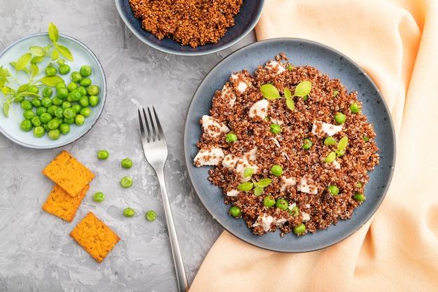 Quinoa-havermoutpap met doperwt en kip op ceramische plaat op een grijze concrete lijst. bovenaanzicht, plat leggen, close-up.