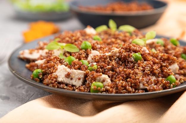 Quinoa-havermoutpap met doperwt en kip op ceramische plaat op een grijze concrete lijst. zijaanzicht, close-up.