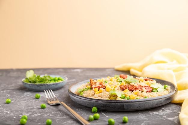 Quinoa pap met groene erwt, maïs en gedroogde tomaten op keramische plaat op een grijze en oranje tafel