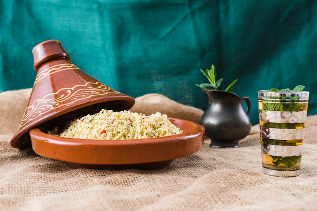 Quinoa salade dichtbij kop en waterkruik op jute