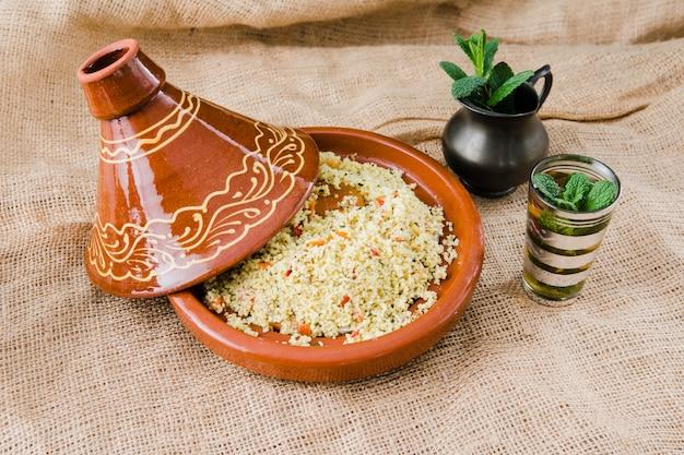 Quinoa salade in kom dichtbij kop en waterkruik