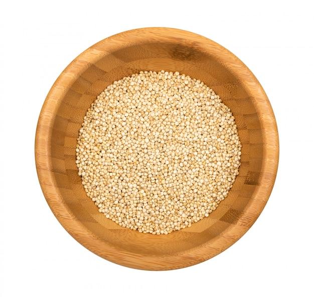 Quinoa zaden in een houten kom geïsoleerd op een witte achtergrond. droge organische chenopodium quinoa granen bovenaanzicht