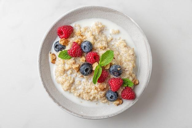 Quinoapap met verse bessen, noten en munt in een kom op witte achtergrond. bovenaanzicht. gezond dieet ontbijt