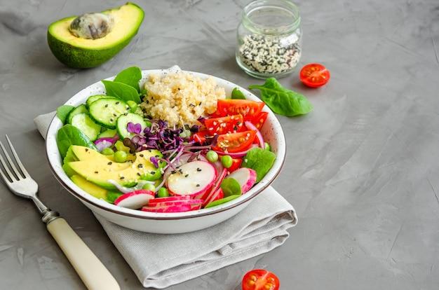 Quinoasalade met verse groenten, spinazie, doperwtjes, microgreens en sesamzaadjes