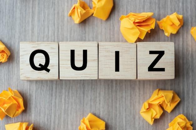 Quiz-tekst houten kubus en verkruimeld papier