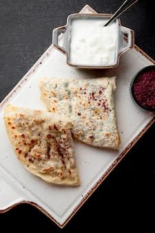 Qutabs geserveerd met yoghurt en berberis