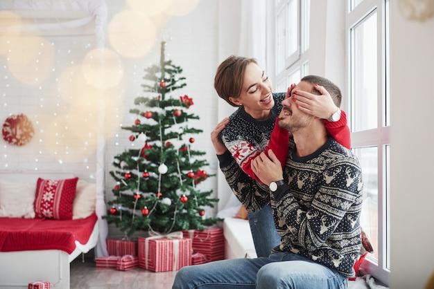 Raad eens welk geschenk ik je zal geven. gelukkige jonge mensen zit op de vensterbank in de kamer met kerstversiering