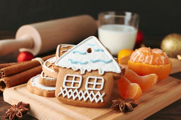 Raad van zelfgemaakte kerstkoekjes, glas melk, mandarijn, kaneel, snoepjes, schommelstoel op houten, close-up