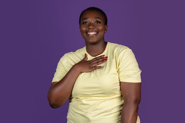 Raadselachtig zicht. halve lengte portret van jonge afrikaanse mooie vrouw geïsoleerd op paarse studio achtergrond. concept van menselijke emoties, gezichtsuitdrukking, schoonheid, mode, jeugd, verkoop. lichaamspositief