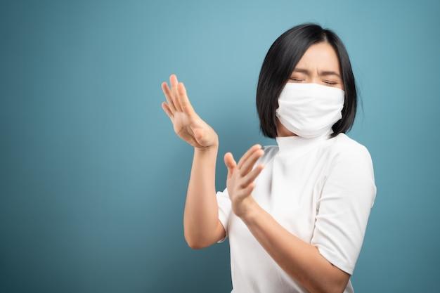 Raak me niet aan. aziatische vrouw die hygiënemasker draagt, paniek en walgt van het teken van het handstop