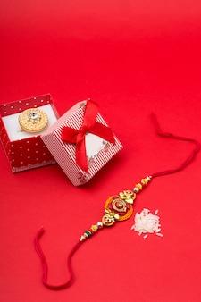 Raakhi en een geschenk voor de zus, gegeven door broer ter gelegenheid van raksha bandhan. indiaas festival raksha bandhan met een elegante rakhi.