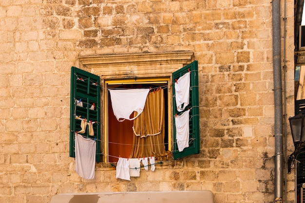 Raam met luiken op het oude gebouw, linnen gedroogd op het raam.