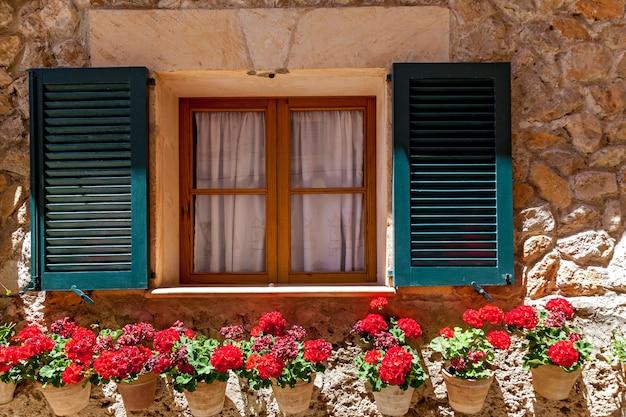 Raam met open luiken en bloeiende bloempotten, venster in bloemen in