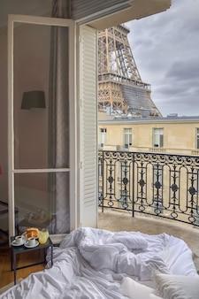 Raamuitzicht op de eiffeltoren met ontbijt op een bed