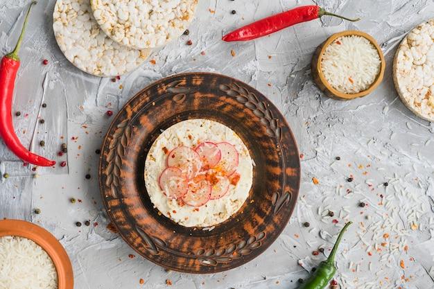 Raapplakken op gepuft rijstkoekjeskruiden met rode spaanse peper en zwarte pepers op concrete achtergrond