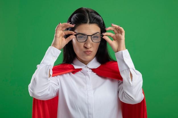 Raar jong kaukasisch superheromeisje die handen op scheve glazen houden die op groene muur worden geïsoleerd