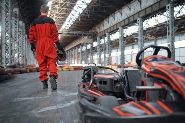 Racer met helm in de buurt van kart-auto, achteraanzicht, karting autosport binnen. snelheidsrace op nauwe kartbaan met bandenbarrière. snelle voertuigcompetitie, vrije tijd met veel adrenaline