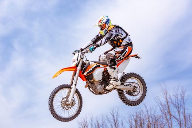 Racer op een motorfiets springt en vertrekt op een springplank