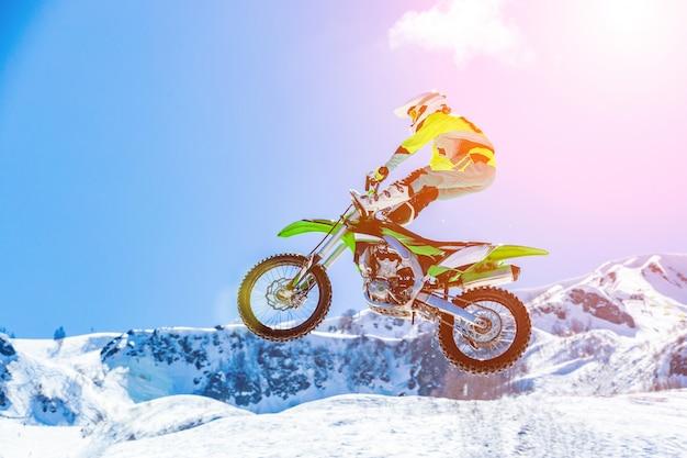 Racer op een motorfiets tijdens de vlucht, springt en vertrekt op een springplank tegen de besneeuwde bergen