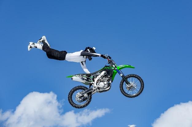 Racer op een motorfiets tijdens de vlucht, springt en vertrekt op een springplank tegen de blauwe hemel
