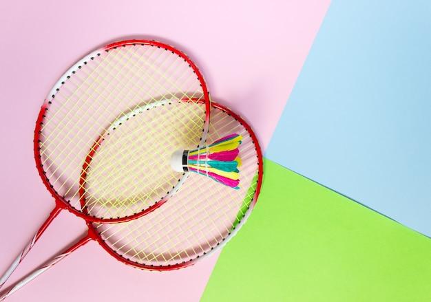 Rackets en een badmintonshuttle op een veelkleurige achtergrond, bovenaanzicht
