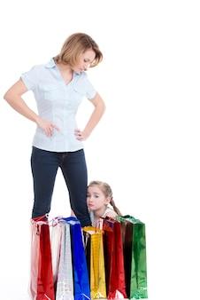 Radeloos meisje zit bij zijn moeder na het winkelen