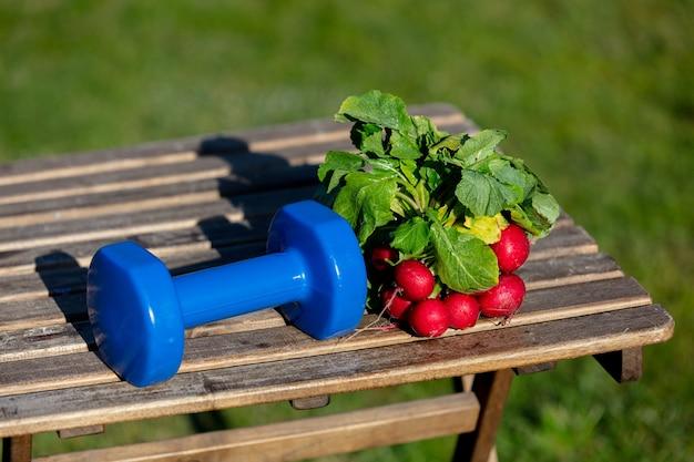 Radijs en dumbells op een houten tafel in een tuin