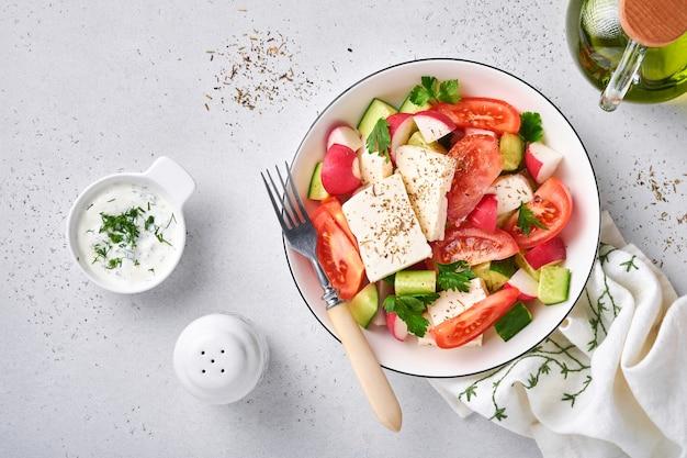 Radijs, komkommer, tomaat, peper en feta-kaas met kruiden, peper en olijfolie in witte kom op grijze leisteen, steen of betonnen ondergrond. gezond voedselconcept. bovenaanzicht.