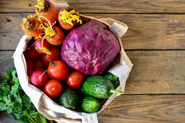 Radijs, tomaten, komkommers, wortelen, rode kool in een zak. bovenaanzicht. stoffen tas gemaakt van linnen.