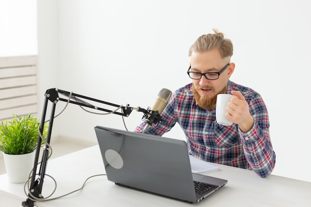 Radio, dj, bloggen en mensen concept - glimlachende man zit microfoon, gastheer op radio