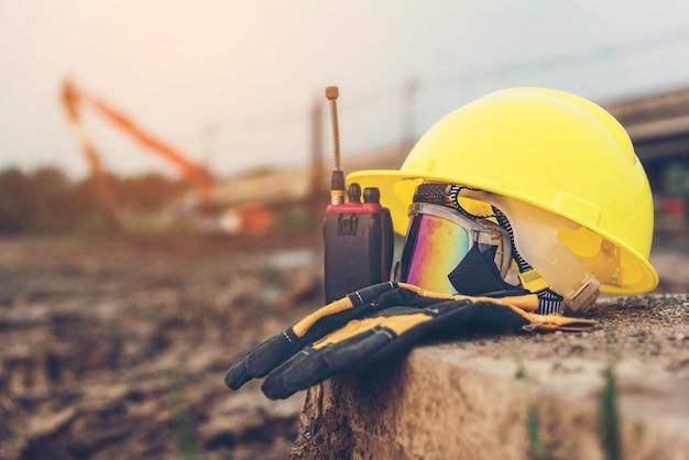 Radiocommunicatie en veiligheidsbril op de cementen vloer.
