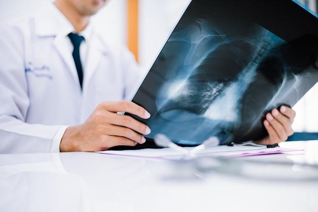 Radiologie arts die bij borst x ray film van patiënt bij gezondheidszorgkliniek onderzoekt