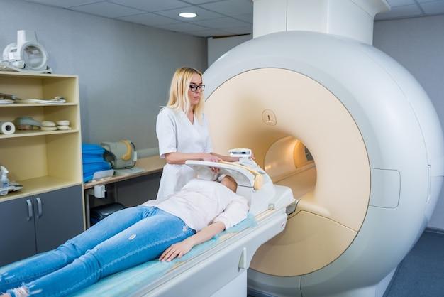 Radioloog bereidt de jonge vrouw voor op een mri-hersenonderzoek