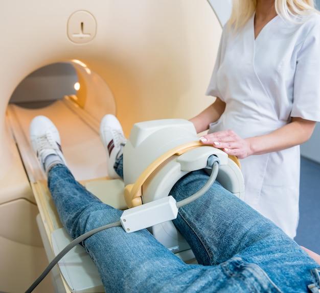 Radioloog bereidt de patiënt voor op een mri-knieonderzoek.