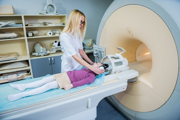 Radioloog bereidt het kleine meisje voor op een mri-hersenonderzoek