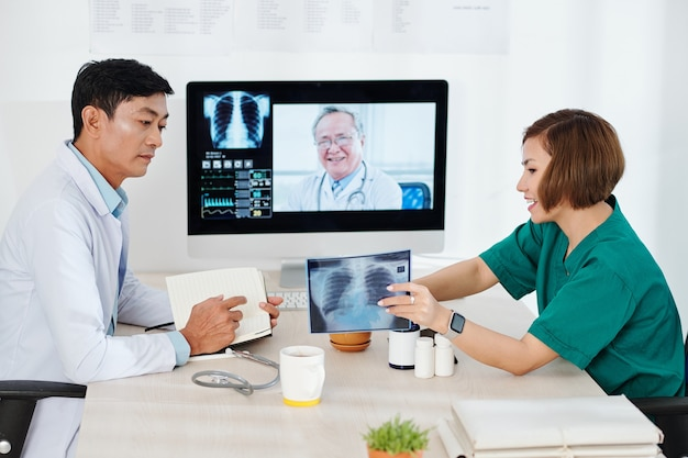Radioloog longen x-ray tonen aan collega tijdens online bijeenkomst met ervaren oncoloog