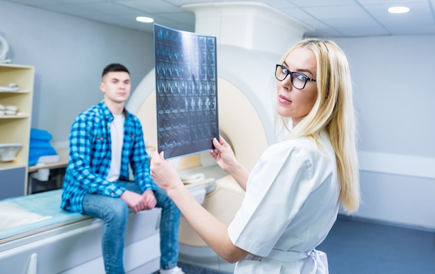 Radioloog met een mannelijke patiënt die een mri-scan onderzoekt.