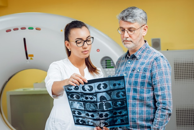 Radioloog met een mannelijke patiënt die röntgenstraal bekijkt.