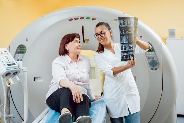 Radioloog met een oudere vrouwelijke patiënt kijken naar x-ray.