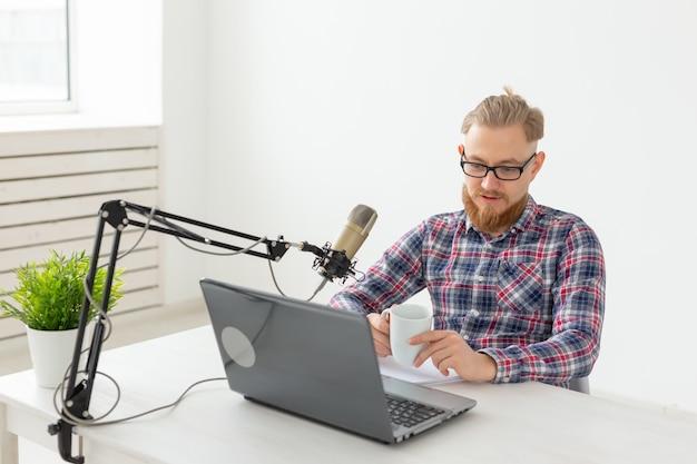 Radiopresentator, streamer en bloggerconcept - knappe man aan het werk als radiopresentator bij een radiostation dat voor de microfoon zit