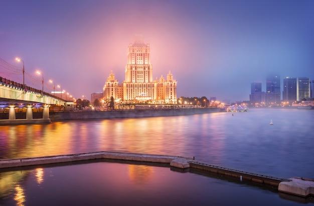 Radisson hotel in moskou in de ochtendnevel en de brug over de rivier de moskva in het licht van lantaarns