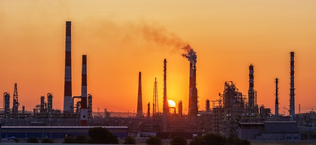 Raffinaderij fabriek silhouet bij zonsondergang
