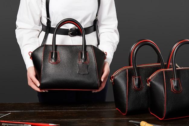 Raftswoman toont nieuwe modieuze handgemaakte handtas in designer workshop Premium Foto