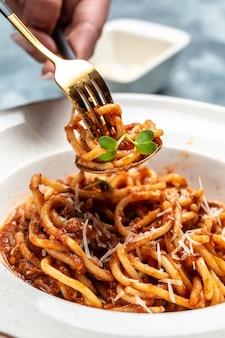Ragu bolognese, italiaanse rundergehaktsaus met spaghettideegwaren en parmezaanse kaas op vork. verticaal beeld.