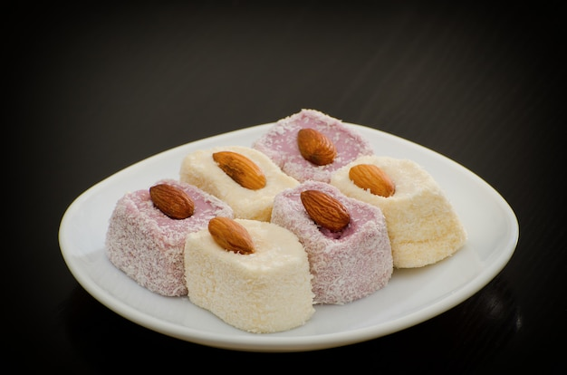 Rahat delight white en blueberry met amandelen, een schoteltje op een zwarte tafel