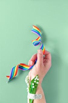 Rainbow lint in de hand. lelietje-van-dalenbloemen bevestigd aan pols met medische patch, hulpband. bedankt dokters, verpleegsters en sleutelwerkers!