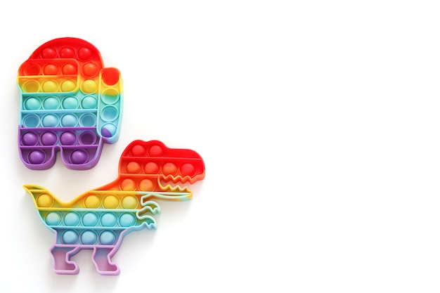 Rainbow pop it fidget speelgoed op witte achtergrond. vrije ruimte, kopieer ruimte. antistress kinderspel. trendy siliconen speelgoed voor kinderen knalt het om stress te verlichten en handmotorische vaardigheden te ontwikkelen.
