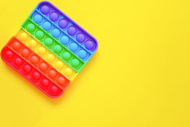 Rainbow pop it toy fidget op een achtergrond van lege kopieerruimte. gele achtergrond