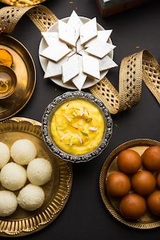 Raksha bandhan-groeten: zoet eten zoals gulab jamun, rasgulla, shrikhand, bundi laddu, kaju katli en farsan met pooja thali voor rakhi festival celebration