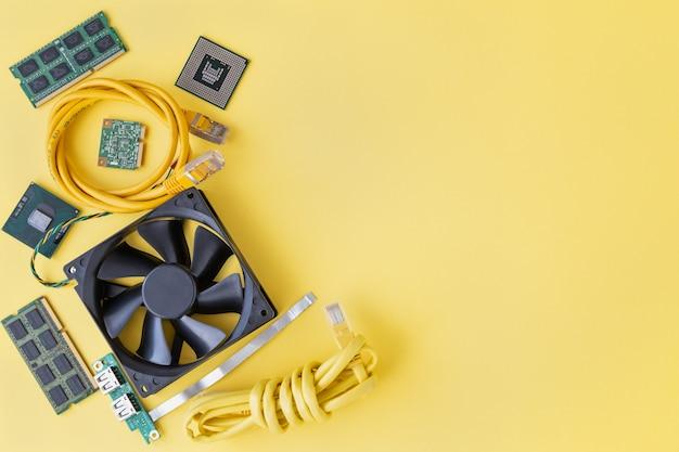 Ram so-dimm, cpu, patchkabel, koeler, usb, wi-fi-module op de gele achtergrond plat